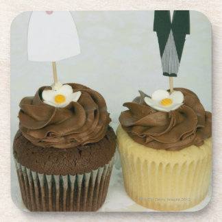 Two cupcakes with toy bride and groom on them beverage coasters