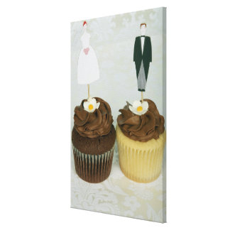 Two cupcakes with toy bride and groom on them stretched canvas prints