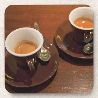 two cups of freshly brewed espresso coffee on a coaster