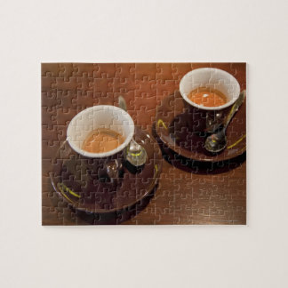 two cups of freshly brewed espresso coffee on a jigsaw puzzle