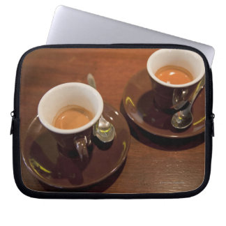 two cups of freshly brewed espresso coffee on a laptop sleeve