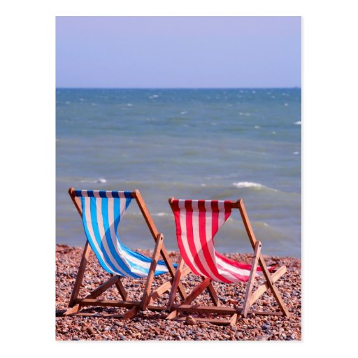 Two deckchairs on the beach post card