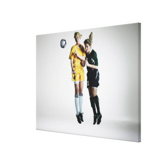 Two female soccer players in mid air heading gallery wrap canvas