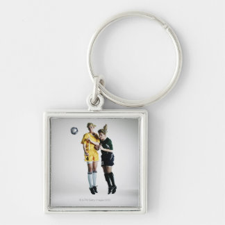 Two female soccer players in mid air heading key ring