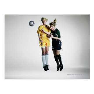 Two female soccer players in mid air heading postcard