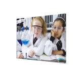 Two girls in school uniform wearing lab coats canvas prints