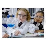 Two girls in school uniform wearing lab coats greeting card