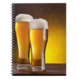 Two glasses of beers on a wooden table notebooks