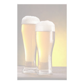 Two glasses of beers on a wooden table stationery
