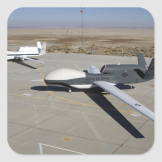 Two Global Hawks parked on a ramp Square Sticker