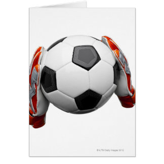Two goal keepers gloves holding a football card