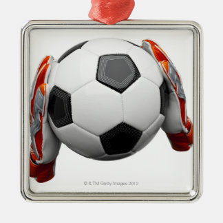 Two goal keepers gloves holding a football christmas ornament