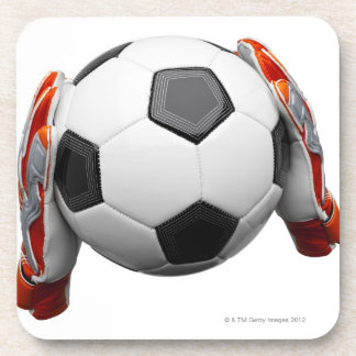 Two goal keepers gloves holding a football coaster