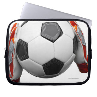 Two goal keepers gloves holding a football laptop sleeve
