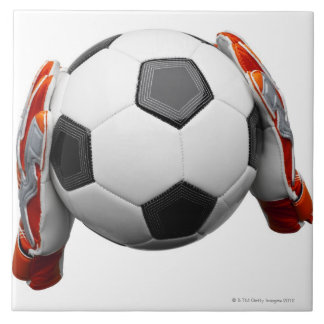 Two goal keepers gloves holding a football large square tile