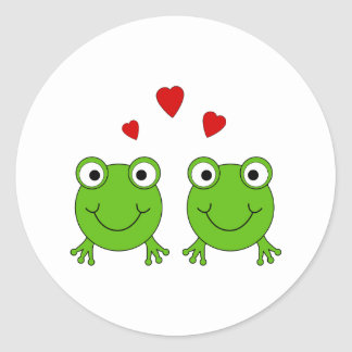 Two green frogs with red hearts. classic round sticker