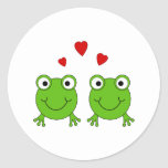 Two green frogs with red hearts. round sticker
