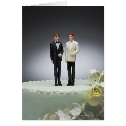 Two groom figurines on top of wedding cake greeting card