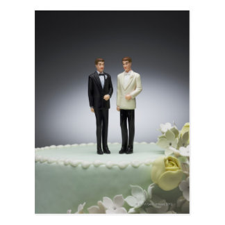 Two groom figurines on top of wedding cake postcard