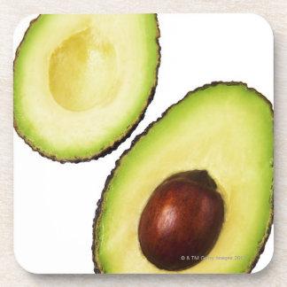 Two halves of an an avocado, on white coaster
