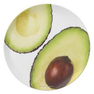 Two halves of an an avocado, on white dinner plate