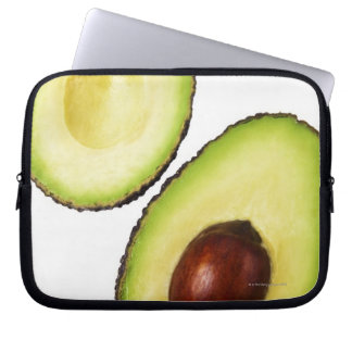 Two halves of an an avocado, on white laptop sleeve