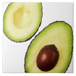 Two halves of an an avocado, on white large square tile