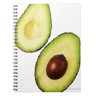 Two halves of an an avocado, on white spiral notebook