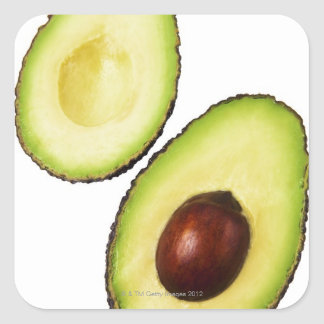 Two halves of an an avocado, on white square sticker