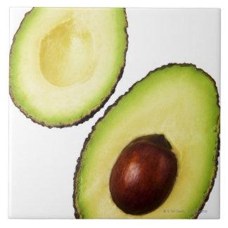 Two halves of an an avocado, on white tile