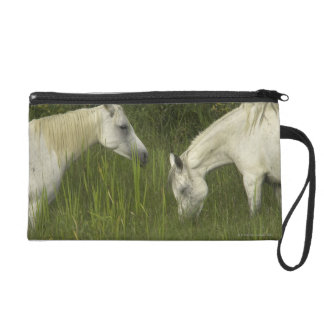 Two horses eating grass wristlet