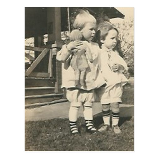 Two kids with a doll outside postcards