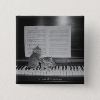 Two kittens sitting on piano keyboard by sheet 15 cm square badge