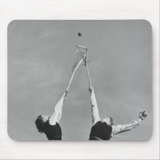Two lacrosse players jump for the ball. mouse pad