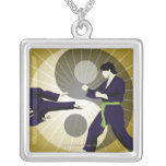 Two men performing martial arts in front of a square pendant necklace