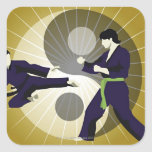 Two men performing martial arts in front of a sticker