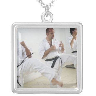 Two mid adult men with a young man practicing personalized necklace