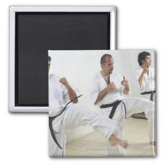 Two mid adult men with a young man practicing square magnet