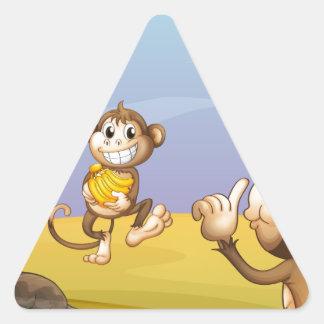 Two monkeys beside the big tree triangle sticker