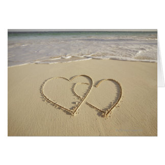 Two overlying hearts drawn on the beach greeting card