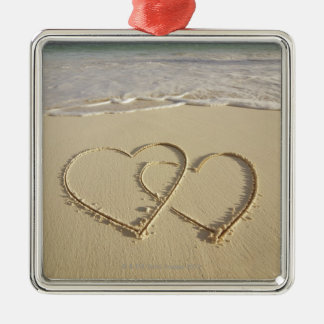 Two overlying hearts drawn on the beach christmas ornament