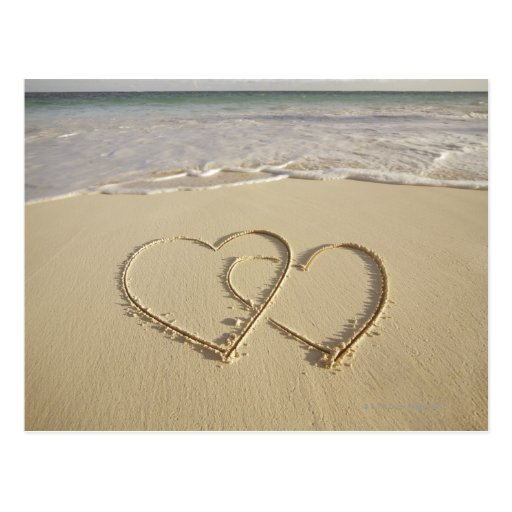 Two overlying hearts drawn on the beach post cards