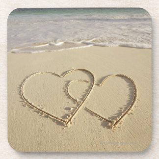 Two overlying hearts drawn on the beach with coaster