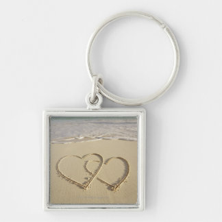 Two overlying hearts drawn on the beach with key ring