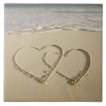 Two overlying hearts drawn on the beach with large square tile
