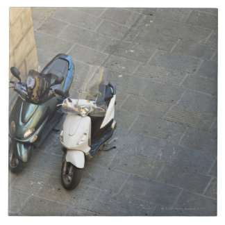 Two parked motor scooters by wall, Siena, Italy Tile