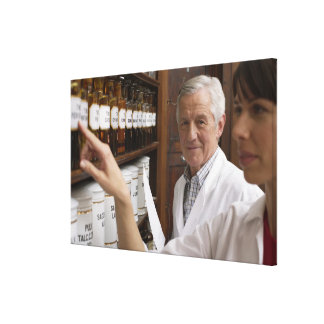 Two pharmacists in front of a shelf with tins canvas print
