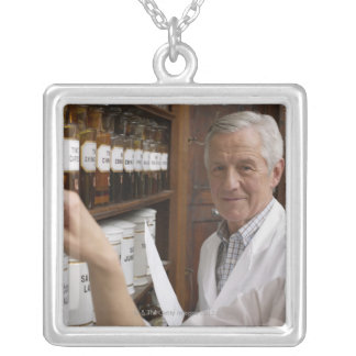Two pharmacists in front of a shelf with tins square pendant necklace