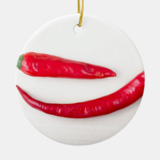 Two red hot chili peppers closeup christmas ornament