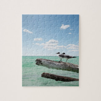 Two seagulls sitting on a dead tree sticking out jigsaw puzzle